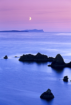 Sunset over Sand Wick and rising moon over Foula in distance, Eshaness, Shetland, Scotland, United Kingdom, Europe