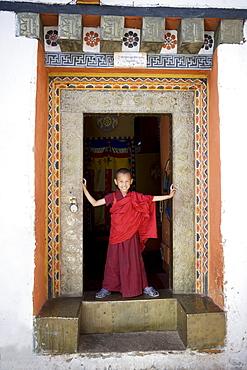 Young Buddhist monk in doorway, Paro Dzong, Paro, Bhutan, Asia
