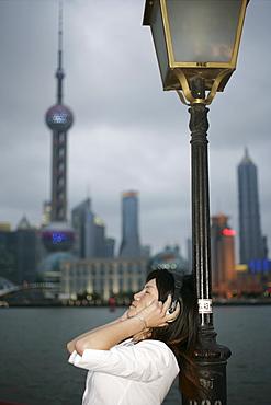 Chinese woman listening to music, the Bund, Shanghai, China, Asia