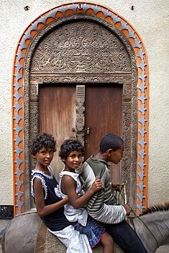 Children in front of a Lamu door, Lamu Town, Lamu, Kenya, East Africa, Africa