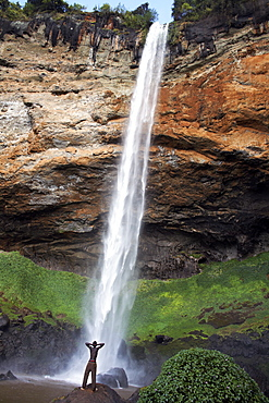 A man looks up at Sipi Falls, Uganda, East Africa, Africa