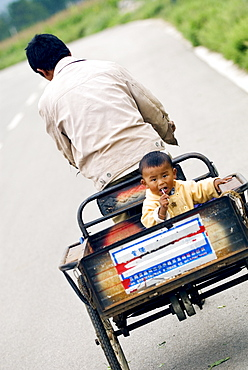 Child being carried on tricycle, Baisha, Yunnan, China, Asia
