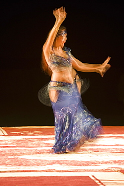 Belly dancer performing a traditional dance in the open air at night, near Abu Dhabi, United Arab Emirates, Middle East