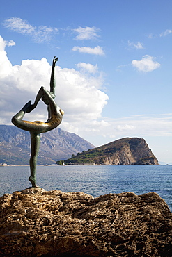 Statue of naked dancing girl on a rock near the Adriatic with Sveti Nikola island in the background, Budva, Montenegro, Europe