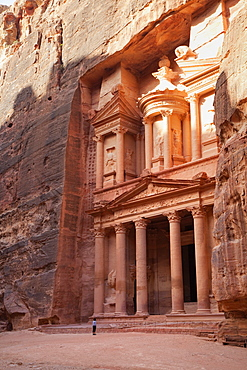 Tourist looking up at the facade of the Treasury (Al Khazneh) carved into the red rock at Petra, UNESCO World Heritage Site, Jordan, Middle East
