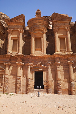 Tourists being photographed at the facade of the Monastery carved into the red rock at Petra, UNESCO World Heritage Site, Jordan, Middle East