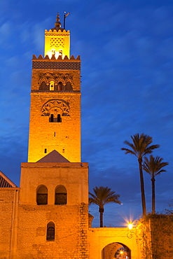 The Minaret of the Koutoubia Mosque illuminated at dusk with palm trees, UNESCO World Heritage Site, Marrakech, Morocco, North Africa, Africa