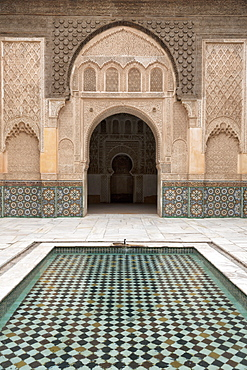 Courtyard and pool with traditional Moroccan ornate doorway in the Ben Youssef Medersa, UNESCO World Heritage Site, Marrakech, Morocco, North Africa, Africa
