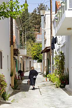 Lady in traditional dress walking in a quiet street in the historic village of Omodos in the Troodos mountains, Cyprus, Europe