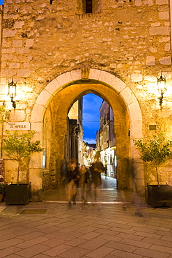 People strolling in the evening, Piazza IX Aprile, gateway through Torre dell Orologio, Taormina, Sicily, Italy, Europe
