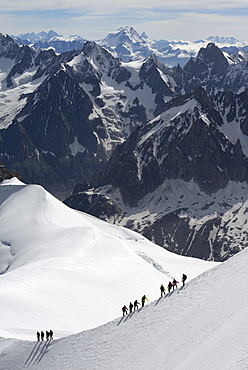 Mountaineers and climbers hiking on a snowy ridge, Aiguille du Midi, Mont Blanc Massif, Chamonix, Haute Savoie, French Alps, France, Europe