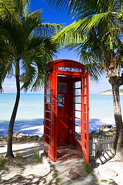 Traditional English red telephone box on the beach at Dickenson Bay, Antigua, Leeward Islands, West Indies, Caribbean, Central America
