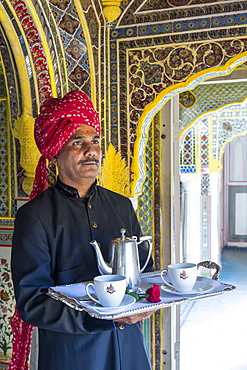 Waiter carrying tea tray in ornate passageway, Samode Palace, Jaipur, Rajasthan, India, Asia