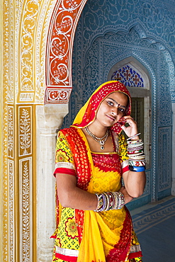 Lady wearing a colourful sari in ornate passageway, Samode Palace, Jaipur, Rajasthan, India, Asia
