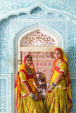 Ladies wearing colourful saris in ornate passageway, Samode Palace, Jaipur, Rajasthan, India, Asia