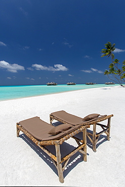 Lounge chairs and tropical beach, water villas and palm trees, Maldives, Indian Ocean, Asia
