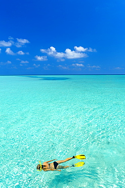 Young woman snorkelling in Maldives, Indian Ocean