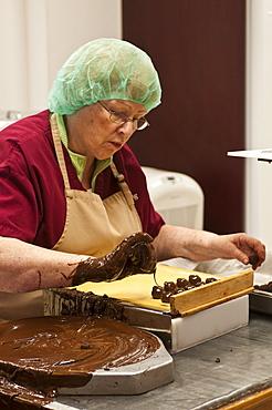 Hand decorating chocolates at the Ganong Chocolate factory, New Brunswick, Canada, North America