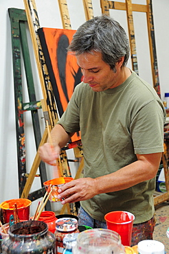 Mexico, Bajio, San Miguel de Allende, Artist Juan Ezcurdia in his studio mixing paint.