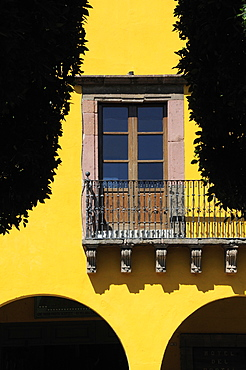 Mexico, Bajio, San Miguel de Allende, El Jardin detail of yellow painted exterior facade of colonial mansion with French windows and balcony part framed by silhouetted trees.