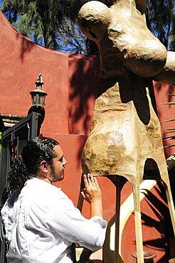 Mexico, Bajio, San Miguel de Allende, Artist Alejandro Lopez with sculpture at his studio.