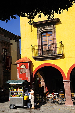 Mexico, Bajio, San Miguel de Allende, El Jardin Part view of yellow painted facade of colonial mansion with French window and balcony with fruit juice vendor in street below.