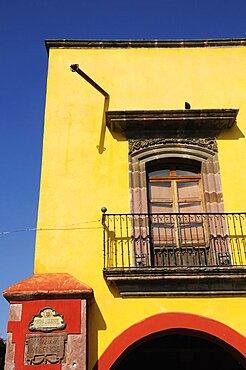 Mexico, Bajio, San Miguel de Allende, El Jardin Part view of yellow painted exterior facade of building with French windows and balcony.