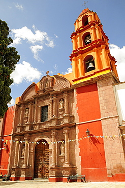 Mexico, Bajio, San Miguel de Allende, Exterior facade and bell tower of orange and yellow painted church building with flags hanging across doorway.