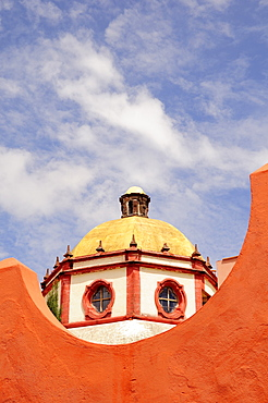 Mexico, Bajio, San Miguel de Allende, Dome of the Parroquia church part framed by orange painted wall.