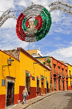 Mexico, Bajio, San Miguel de Allende, Independence Day decorations adorn colonial street lined by colourful buildings.