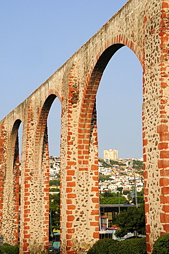 Mexico, The Bajio, Queretaro , Aquaduct arches framing view towards city buildings on hillside beyond.