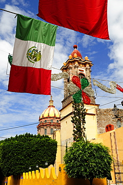 Mexico, Bajio, San Miguel de Allende, Mexican flags and Independence Day decorations hang in foreground of church.