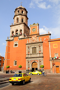 Mexico, Bajio, Queretaro, The church of San Francisco brightly coloured exterior facade with taxis and cyclist on road in foreground.