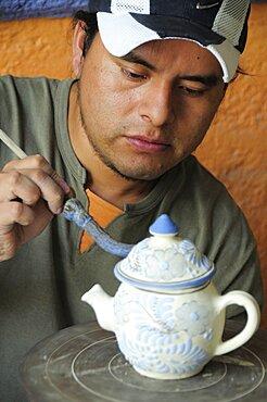 Mexico, Puebla, Talavera ceramic artist at Armando Gallery applying blue detail to raised design on teapot.