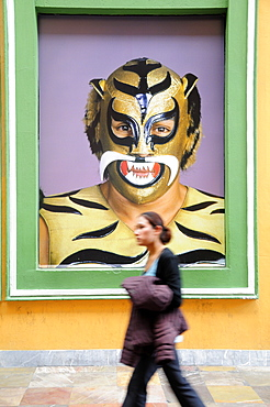 Mexico, Puebla, Young girl walking past poster of wrestler wearing mask and costume.