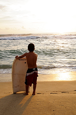 Mexico, Oaxaca, Puerto Escondido, Playa Zicatela Young body boarder standing on beach looking out to sea.