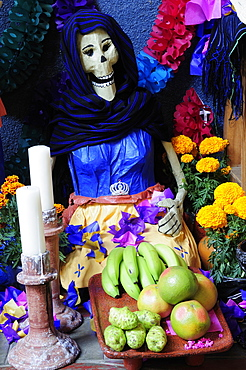 Mexico, Michoacan, Patzcuaro, Dia de los Muertos Day of the Dead altar with figures food candles and flowers.