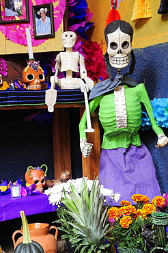 Mexico, Michoacan, Patzcuaro, Dia de los Muertos Day of the Dead altar with skeleton figures flowers and colourful paper decorations.