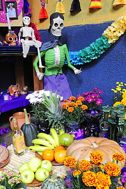 Mexico, Michoacan, Patzcuaro, Dia de los Muertos Day of the Dead altar with skeleton figures food and drink and colourful paper decorations.