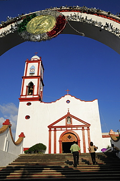 Mexico, Veracruz, Papantla, Cathedral de la Asuncion white and red painted exterior bell tower and steps to entrance framed by arch decorated for Independence Day celebrations.