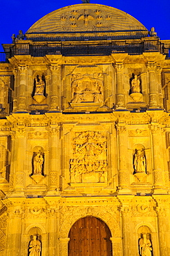 Mexico, Oaxaca, Part view of baroque exterior facade of cathedral at night with relief carving of the assumption of the Virgin Mary above door.