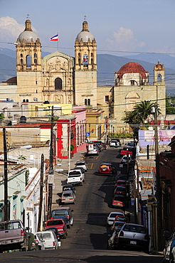 Mexico, Oaxaca, View along street lined with parked vehicles towards church of Santo Domingo.
