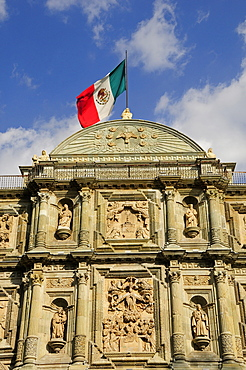 Mexico, Oaxaca, Cathedral facade with Mexican flag flying from roof.