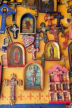 Mexico, Michoacan, Patzcuaro, Religious kitsch art displayed on yellow painted wall.