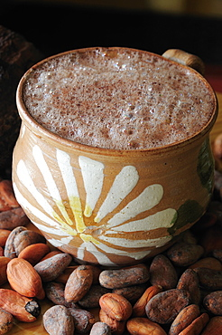 Mexico, Oaxaca, Chocolate caliente hot chocolate in painted cup with cocoa beans.