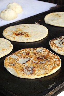 Mexico, Bajio, San Miguel de Allende, Cooking tortillas on griddle.