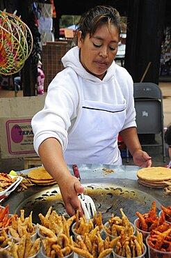 Mexico, Michoacan, Patzcuaro, Young woman frying fish.