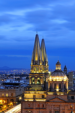 Mexico, Jalisco, Guadalajara, Cathedral domed roof and bell towers at night with city spread out behind.