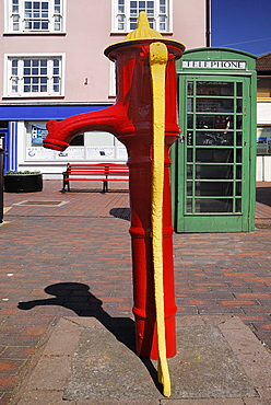 Ireland, County Cork, Kinsale, Colourful old water pump and telephone box .