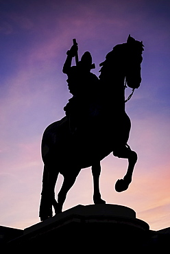 Spain, Madrid, Statue of King Philip II in Plaza Mayor silhouetted against evening sky.